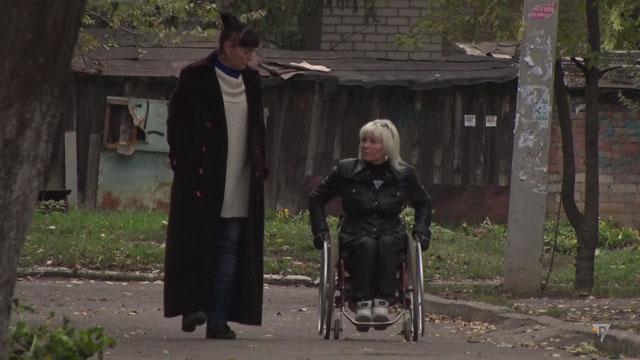 """Нескорені"" Надія Дмитрук (ВІДЕО). надія дмитрук, здоровий, обмеженими фізичними можливостями, суспільство, хвороба, outdoor, ground, grass, clothing, person, jacket. A person standing in front of a building"