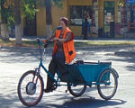 В Мариуполе велорикши помогают людям с ограниченными возможностями (ВИДЕО). мариуполь, свет маяка, велорикша, доставка, инвалидность, outdoor, bicycle, road, street, wheel, person, vehicle, bicycle wheel, land vehicle, cart. A person riding a bicycle on a city street