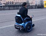 "В Швейцарії винайшли гусеничний візок-""всюдихід"" для людей з обмеженими можливостями (ВІДЕО). scewo, швейцария, винахід, обмеженими можливостями, інвалідний візок-всюдихід, outdoor, road, ground, wheel, land vehicle, street, vehicle, transport, luggage and bags, sidewalk. A person riding a motorcycle on a city street"
