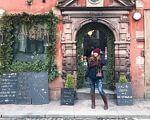 Нечуючі у світі. Погляд українки на досвід Швеції. швеція, нечуючий, пенсія, порушення слуху, інвалідність, building, outdoor, ground, stone, door, jeans, footwear, clothing. A person standing in front of a stone building