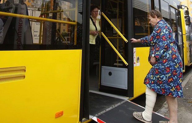 На програму перевезення людей з інвалідністю виділено 30 млн грн. андрій рева, доступність, перевезення, транспорт, інвалідність, person, indoor, clothing, standing, bus, yellow. A person standing in front of a bus
