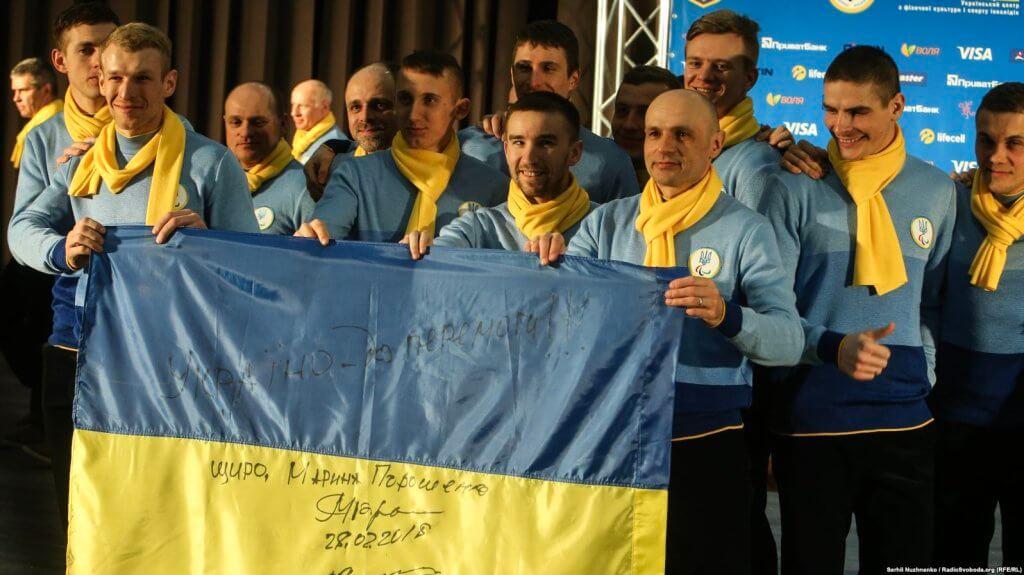 У Пхьончхані відбулася церемонія відкриття XІІ зимових Паралімпійських ігор. паралімпійські ігри, атлет, змагання, паралимпиец, спортсмен, person, human face, clothing, man, smile, group, people, yellow. Vitaliy Lukyanenko et al. standing in front of a crowd