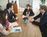 """В Мінсоцполітики триває реалізація проекту TWINNING «Підтримка органів влади України в розробці законодавчих та адміністративних засад для запровадження системи раннього втручання та реабілітації дітей з інвалідністю і дітей, які мають ризик отримати інвалідність"""". проект twinning, зустріч, раннє втручання, реалізація, інвалідність, person, clothing, suit, woman, man, table, computer. A group of people standing around a table"""