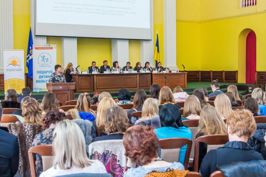 Прес-реліз: Українські спеціалісти вимагають посаду асистента дитини. асистент дитини, особливими освітніми потребами, соціалізація, тьютор, інклюзія, person, clothing, people, woman, group, human face, event, crowd. A group of people sitting at a table in front of a crowd
