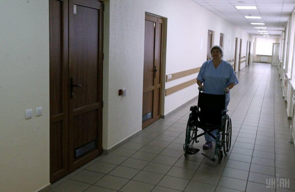 Кабмін запровадив нову модель забезпечення ряду послуг для людей з інвалідністю. електронний каталог, забезпечення, засоби реабілітації, засідання уряду, інвалідність, floor, indoor, wall, building, furniture, chair, wheelchair. A person standing in a room