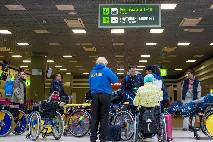 Подорожуємо світом без перешкод. аеропорт, літак, обмеженими можливостями, пасажир, перевезення, person, ceiling, luggage, indoor, sports equipment, airport, bicycle wheel, cart, pulling, land vehicle. A group of people standing around a luggage carousel at an airport
