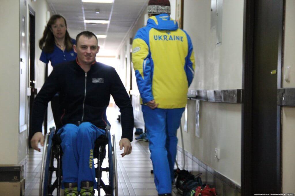 Головне – працювати і себе перебороти – паралімпієць Максим Яровий (ВІДЕО). максим яровий, паралімпійські ігри, паралимпиец, спортсмен, інвалідність, person, clothing, wall, indoor, luggage, wheelchair, man. A person standing next to a bag of luggage