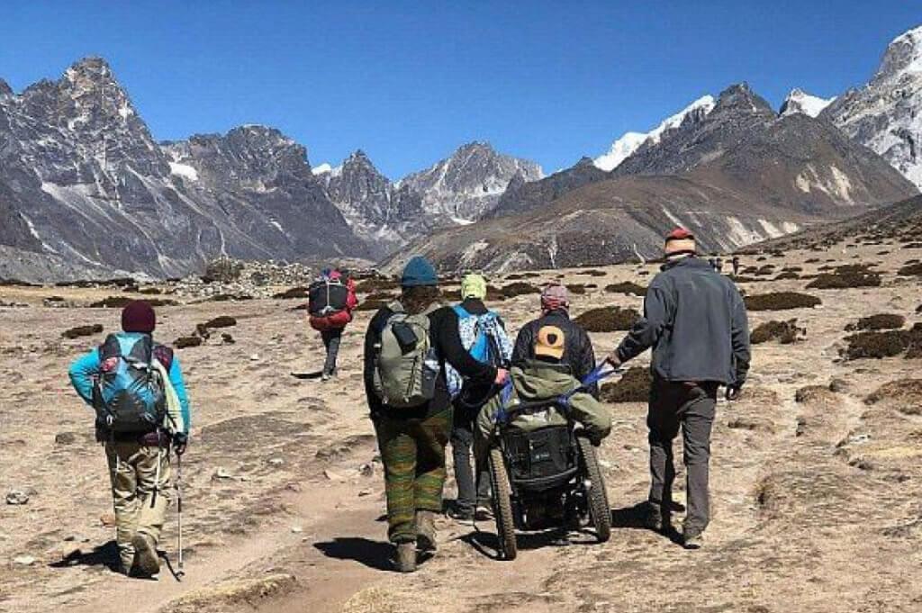 Австралієць з інвалідністю підкорив Еверест, незважаючи на зламаний візок. еверест, автокатастрофа, турист-екстремал, інвалідний візок, інвалідність, sky, hiking, mountain, outdoor, ground, person, hiking equipment, group, people, clothing. A group of people standing on top of a mountain