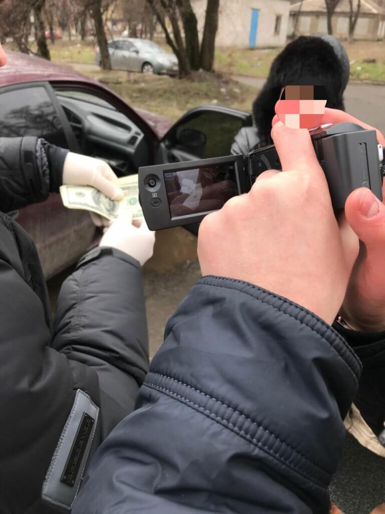 У Маріуполі на отриманні хабара у сумі 1000 доларів США викрито посадову особу Обласної медико-соціальної експертної комісії (ФОТО). мариуполь, омсек, неправомірна вигода, хабар, інвалідність, person, outdoor, cellphone, phone, camera, watch. A man talking on a cell phone
