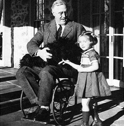 """""""В'яжіть вузол на кінці мотузки і… тримайтесь"""" – як Франклін Рузвельт став зразком нескореного духу. президент сша, франклін рузвельт, поліомієліт, інвалідний візок, інвалідність, person, clothing, outdoor, black and white, smile, human face, baby, furniture, footwear, chair. A man and a woman sitting on a bench"""