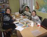 Товариство інвалідів допомагає переселенцям. го ніжність, горішні плавні, переселенец, інвалідність, інтеграція, table, indoor, sitting, person, human face, clothing, smile, family, woman, child art. A group of people sitting at a table