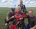 71-річна українка на уродини замовила стрибок з парашутом. Її мрія здійснилася (ФОТО). мрія, парашут, стрибок, інвалідне крісло, інвалідність, grass, outdoor, sky, person, clothing, bicycle, bicycle helmet, sports equipment, helmet, hiking. A group of people sitting on a motorcycle