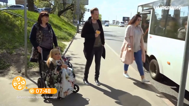Челендж: подорож Києвом на інвалідному візку (ВІДЕО). київ, доступність, комфорт, транспорт, інвалідний візок, clothing, outdoor, footwear, woman, person, jacket, trousers, jeans, car, coat. A group of people walking down a street