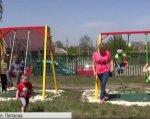 Не війною єдиною: активісти з Попасної узялися обладнати ігровий майданчик для дітей з інвалідністю. попасна, активіст, будівництво, ігровий майданчик, інвалідність, outdoor, grass, sky, person, sport, tree, outdoor play equipment, track and field, footwear, outdoor object. A group of people on a swing