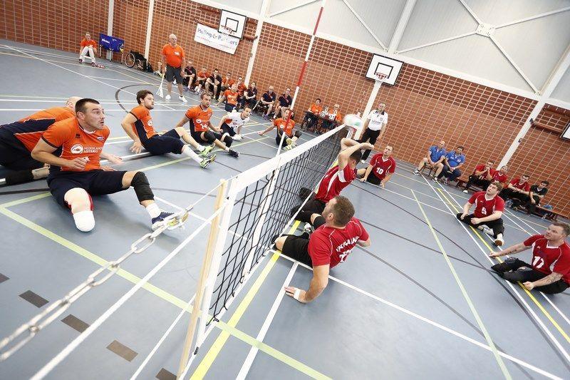 Чоловіча команда з волейболу сидячи стала першою, а жіноча – четвертою на міжнародному турнірі. нідерланди, волейбол сидячи, змагання, команда, турнір, floor, sports equipment, indoor, footwear, person, tennis, sport, sports, orange, racket. A group of people on a court