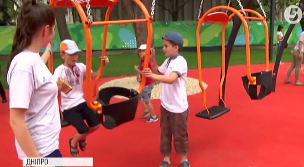 Майданчик рівних можливостей: у Дніпрі відкрили перший в Україні інклюзивний парк для дітей (ВІДЕО). дніпро, соціалізація, суспільство, інвалідність, інклюзивний парк, playground, person, toddler, baby, clothing, outdoor play equipment. A person on a court