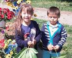 """""""Для мене вона найкраща, моя донечка, мамина принцеса"""": Інтерв'ю із мамою особливої дитини, яка прагне змін і робить своїх дітей щасливими. генетична недуга, неприйняття, нерозуміння, синдром дауна, суспільство, person, grass, outdoor, flower, little, clothing, smile, toddler, human face, plant. A little boy that is standing in the grass"""