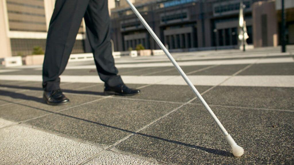 Уже тиждень у Вінниці працює Муніципальна служба супроводу осіб з інвалідністю по зору I групи. вінниця, одержувач, послуга, супровід, інвалідність, road, outdoor, trousers, footwear, person, sidewalk, way, jeans, street, clothing. A person standing on a sidewalk