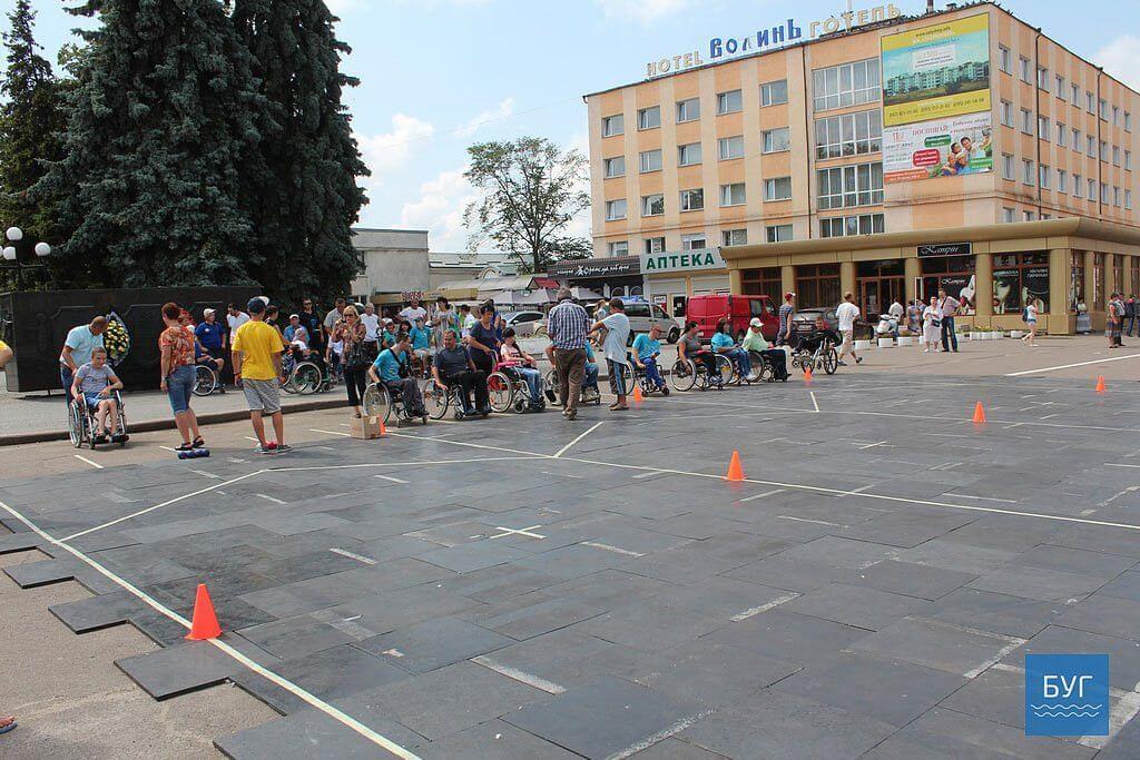 У Володимирі-Волинському вперше провели змагання із гри «Бочча» для людей з обмеженими можливостями (ФОТО). володимир-волинський, бочча, гра, змагання, інвалід, road, outdoor, person, sky, way, marathon, sidewalk, people, scene, parade. A group of people standing in a parking lot