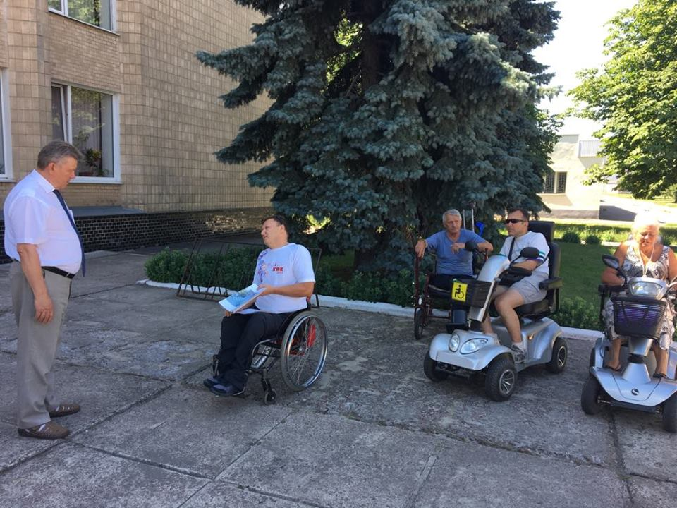Шосткинские колясочники провели акцию протеста возле мэрии. шостка, доступность, инвалидность, пандус, протест, outdoor, tree, wheelchair, person, wheel, people. A group of people riding on the back of a motorcycle