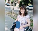 Діагноз – не вирок: вражаюча історія Лілії Процак (ВІДЕО). лілія процак, вирок, діагноз, інвалідний візок, історія, person, girl, clothing, woman, human face, smile, screenshot, car, dress. A screen shot of a woman