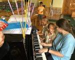 Прес-реліз: В столиці будуть вчити комунікувати дітей з аутизмом за допомогою музики. kidsautismmusic, аутизм, комунікація, освітньо-терапевтична ініціатива, столиця, person, music, indoor, musical keyboard, musical instrument, keyboard, organ, piano. A group of people sitting at a piano