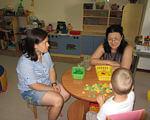 Відділення комплексної реабілітації дітей з інвалідністю запрошує дітей з інвалідністю та дітей віком до трьох років, які належать до групи ризику щодо отримання інвалідності, для проходження реабілітації. южноукраїнськ, діагностика, обстеження, раннє втручання, інвалідність, person, indoor, wall, child, sitting, floor, human face, clothing, toddler, classroom. A small child sitting on a table