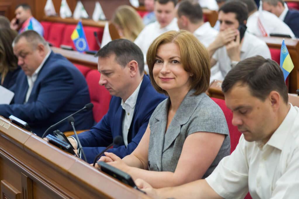 Київ виділив 42 млн грн на створення безбар'єрного простору в столичних школах. ірц, київ, пандус, школа, інклюзія, person, human face, clothing, laptop, smile, indoor, man, computer, woman, suit. A group of people looking at a laptop