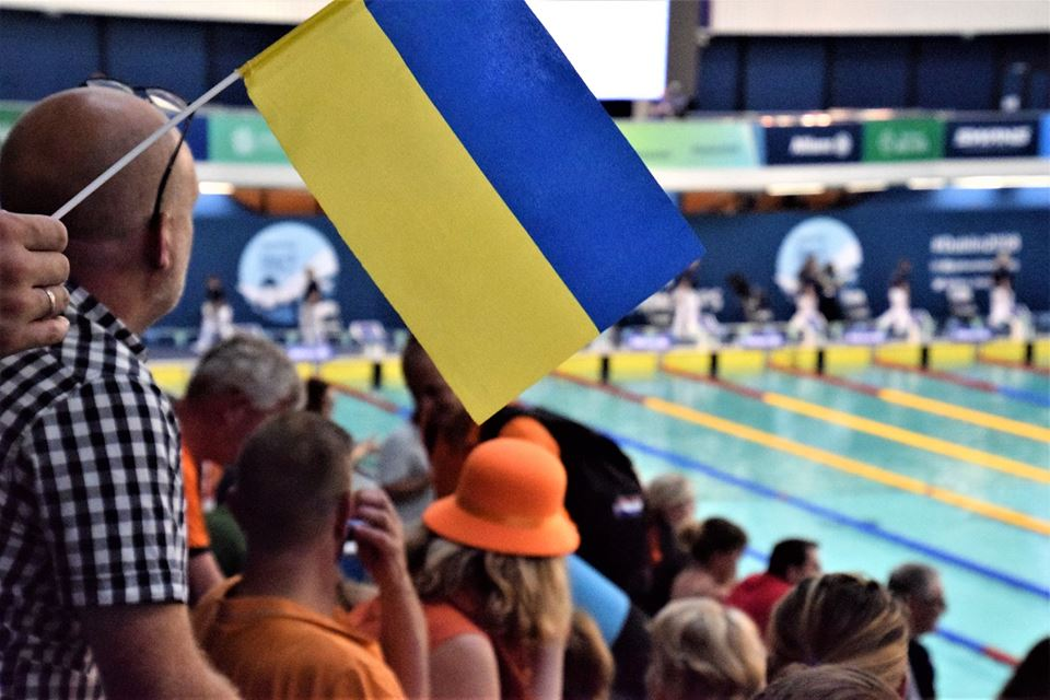 Національна паралімпійська збірна команда з плавання – перша в Європі. змагання, паралімпійська збірна, плавання, спортсмен, чемпіонат європи, person, clothing, hat, human face, fashion accessory, man, people, crowd. A group of people standing in front of a crowd