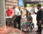 Как в Запорожье опекаются проблемами людей с инвалидностью: впервые за четыре года запорожанка вышла из собственной квартиры (ВИДЕО). запорожье, доступ, инвалидность, пандус, травма, person, outdoor, clothing, footwear, man, people. A group of people sitting in front of a building