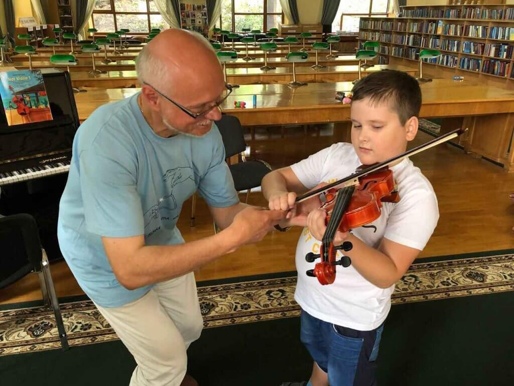 В столице стартовал проект Kids Autism Music & Art. kids autism music & art, киев, рас, музыка, проект, person, music, indoor, bowed instrument. A young boy holding a guitar