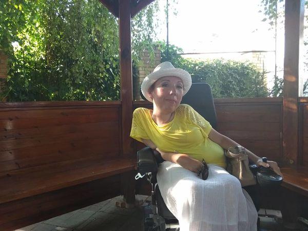 «У мене була така жага до життя, що я не могла всидіти вдома». наталія чущенко, смд, діагноз, суспільство, інвалідність, window, tree, person, clothing, human face, hat, smile, fashion accessory, sun hat. A person sitting in front of a window