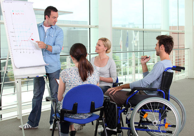 Професійне навчання: цьогоріч понад 60 громадян з інвалідністю здобули нову освіту. кіровоградська область, конкурентоспроможність, профнавчання, центр зайнятості, інвалідність, person, wheelchair, clothing, chair, woman, cart. A group of people looking at a laptop