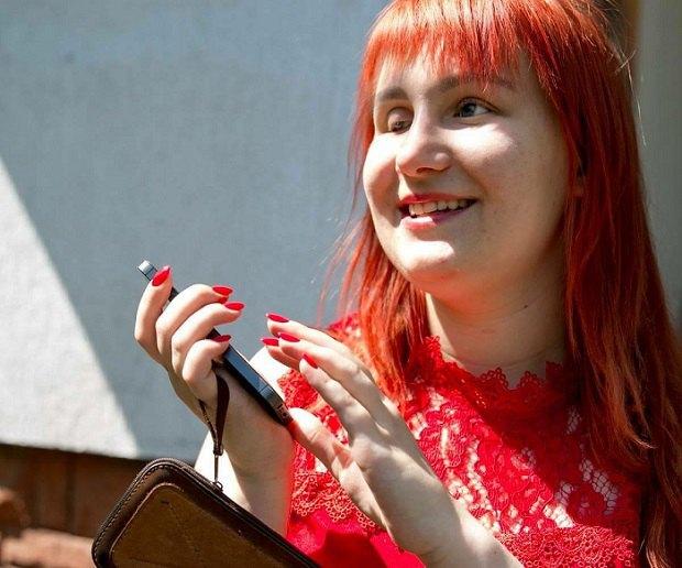 Дарія Коржавіна: «У мене з дитинства виникало питання «Чому придумали сходи?». дарія коржавіна, журналістка, порушення зору, працевлаштування, інвалідність, person, human face, smile, clothing, outdoor, girl, red. A woman holding a cell phone