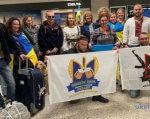 Українські воїни прибули до США для участі в 43 Марафоні Морської піхоти (ВІДЕО). марафон морської піхоти, сша, воїн, поранення, інвалідність, person, clothing, smile, indoor, woman, man, ceiling, human face, group, posing. A group of people posing for the luggage