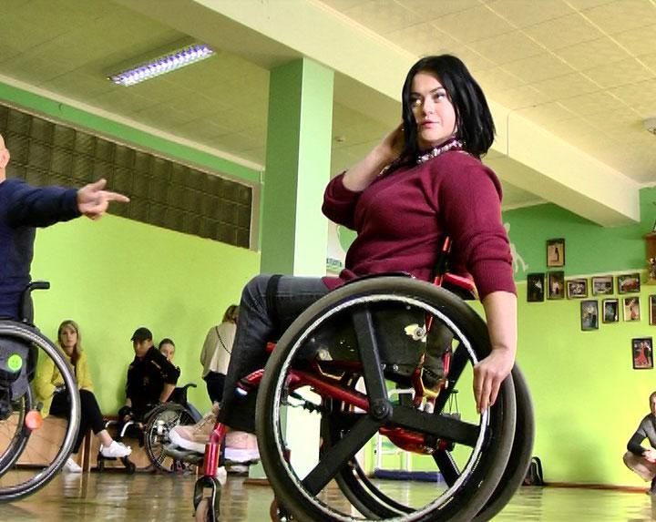 """Вінничани на візках представлятимуть Україну на Міжнародному фестивалі """"Іверія — Брілліант"""". тбілісі, підготовка, турнір, фестиваль іверія — брілліант, інвалідний візок, person, indoor, wheelchair, ceiling, clothing. A woman standing next to a bicycle"""