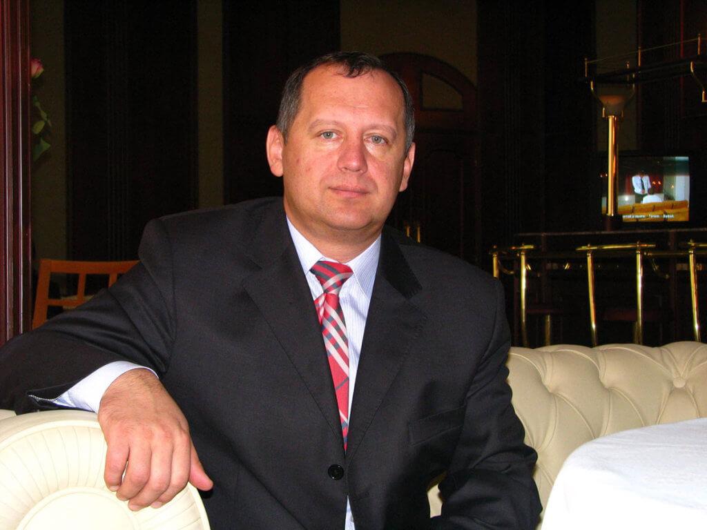 Накопительное страхование для детей с аутизмом. александр саган, рас, аутизм, накопительное страхование, полис, person, man, indoor, wall, human face, clothing, tie, suit. A man wearing a suit and tie
