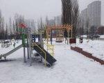 В Киеве создали инклюзивную зону здоровья. киев, барьер, горка, детская площадка, качели, snow, outdoor, sky, tree, playground, winter, cold, bench, day. A building covered in snow