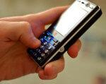Кому из инвалидов в Украине компенсируют стоимость мобильного телефона. аудиоплеер, инвалид, компенсація, мобильный телефон, часы, person, holding, hand, mobile phone, remote, electronics, portable communications device, control, phone, gadget. A hand holding a remote control