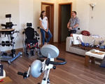 В Одесі відкрили зал фізичної терапії для осіб із обмеженими можливостями (ВІДЕО). одеса, зал фізичної терапії, обладнання, пацієнт, фахівець, indoor, wall, floor, chair, living, room, exercise equipment, table, desk, wheelchair. A group of people in a living room