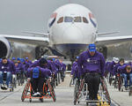 Объединив усилия, люди в инвалидных колясках протащили самолёт более чем на 100 метров (ФОТО, ВИДЕО). англия, инвалидная коляска, инвалидность, рекорд, самолёт, road, vehicle, automaton. A group of people standing around a plane