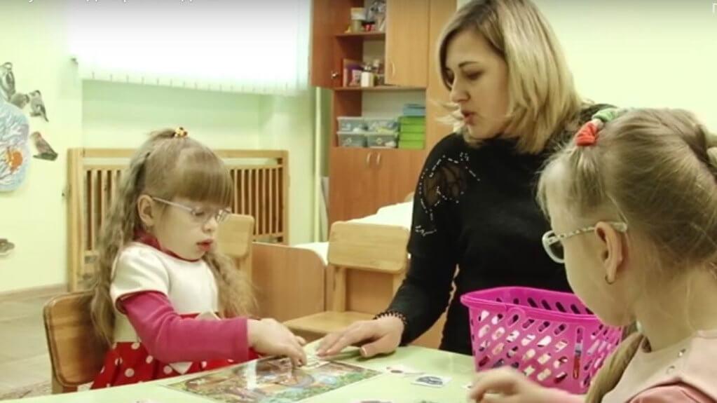 Дошкільна інклюзія – вже не ілюзія у Краматорську. краматорськ, дитсадок, особливими освітніми потребами, інвалідність, інклюзія, person, indoor, clothing, human face, toddler, girl, book, woman. A little girl sitting at a table