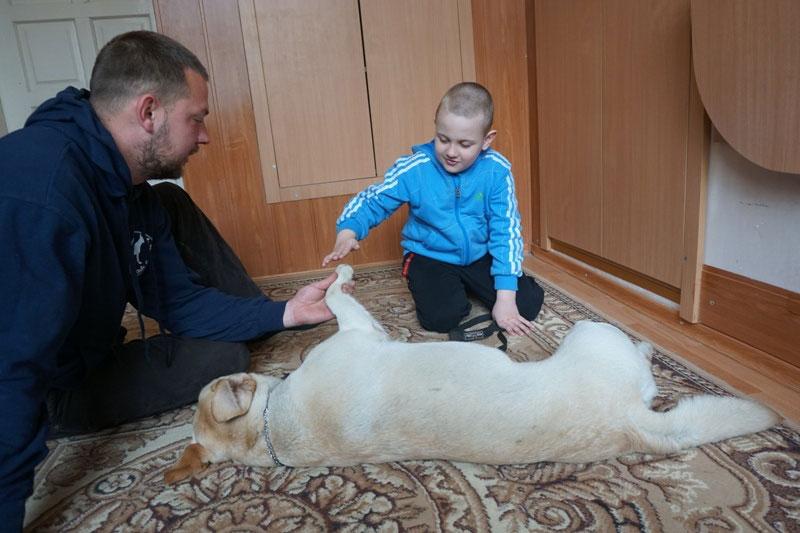 Як собака «лікує» особливих діток у Центрі реабілітації в Чернівцях (ФОТО). чернівці, взаємодія, канистерапия, собака, інвалідність, person, indoor, dog, human face, toddler, clothing, baby, mammal, petting. A man petting a dog