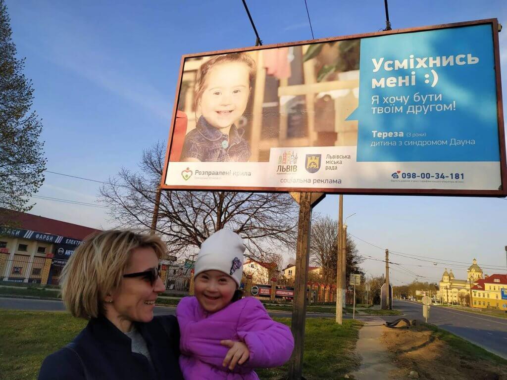 """""""Мама сказала, що ти даун, щоб я з тобою не дружив, бо можна заразитись…."""". го розправлені крила, гідність, особливість, синдром дауна, інвалідність, sky, outdoor, person, human face, grass, billboard, smile, clothing, sign, tree. A person holding a sign"""
