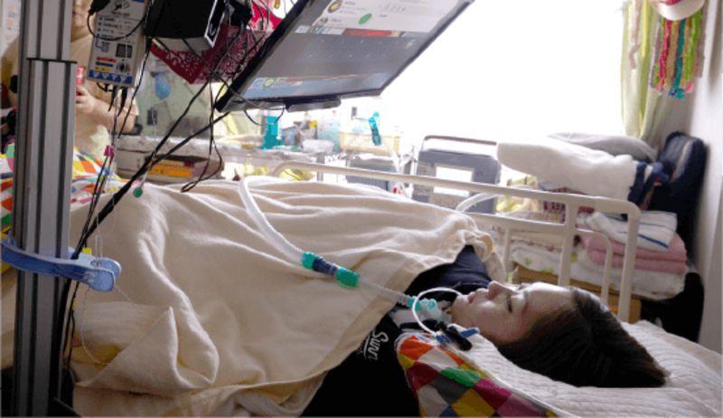 Кафе в Японії бере на роботу лежачих інвалідів: вони керують роботами-офіціантами (ВІДЕО). orihime-d, японія, кафе, офіціант, робот, indoor, bed, laying, baby, clothing, lying, person, messy, cluttered. A little girl lying on a bed
