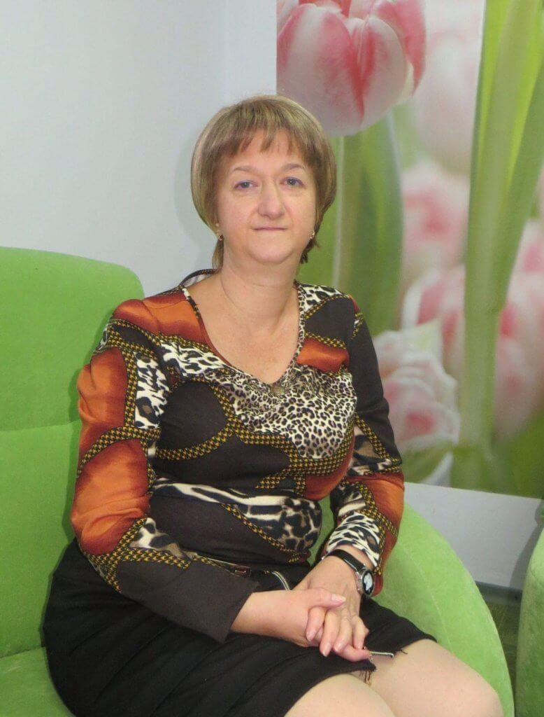 Жительница Бердянска занимается любимым хобби, не смотря на инвалидность. лилия волкова, инвалидность, талант, танець, творчество, person, indoor, human face, clothing, woman, fashion accessory, smile, dress. A woman sitting on a couch