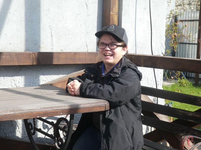«Я ніколи навіть не відчував, що не такий, як усі». максим шостацький, дистрофічна дисплазія, діагноз, спортсмен, інвалідність, fence, bench, outdoor, person, clothing, wooden, smile, furniture, glasses, table. A woman sitting on a wooden bench
