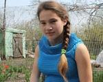 Школярка з Осокорівки вишиває… однією рукою. аліна ярмак, бісероплетіння, вишивання, парез ерба-дюшенна, інвалідність, person, outdoor, clothing, human face, smile, girl, knit, flower. A little girl standing in front of a fence