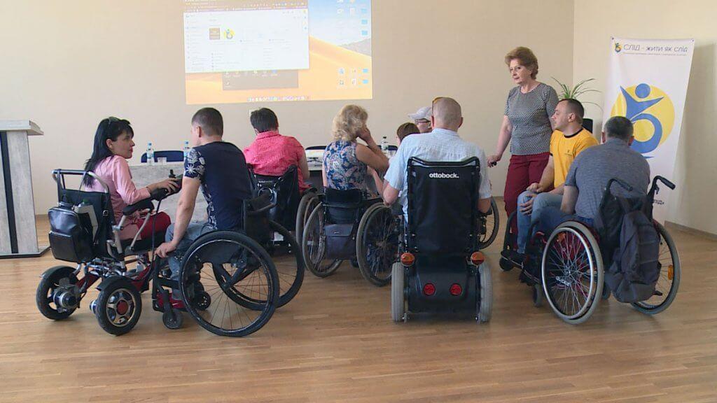 У Коломиї провели навчальний курс «Інвалідність – не обмежує, обмежує дискримінація» (ВІДЕО). коломия, доступ, навчальний курс, суспільство, інвалідність, wheelchair, person, group, clothing, disabled sports, seat. A group of people standing in a room