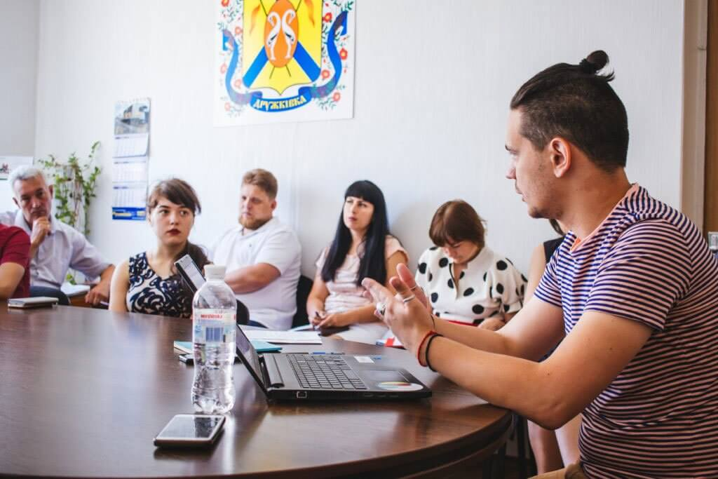 У Дружківці пройде аудит доступності. дружківка, аудит, доступність, круглий стіл, інвалідність, person, indoor, table, human face, laptop, clothing, computer, woman, man. A group of people sitting at a table in front of a laptop